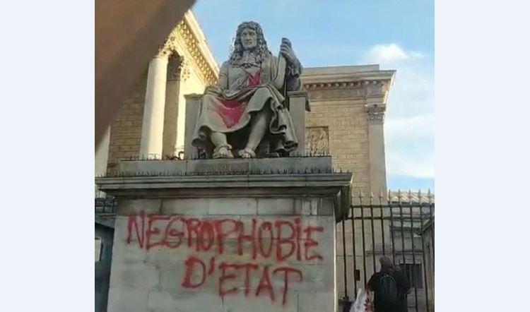 Un graffiti et de la peinture rouge sur la statue de Colbert devant l'Assemblée nationale